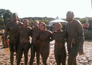 A very muddy group of young professionals post-run